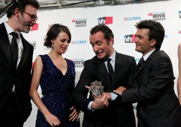 """Actor Dujardin holds the best picture award for """"The Artist"""" as they celebrate their win backstage at the 2012 Critics' Choice Awards in Los Angeles"""