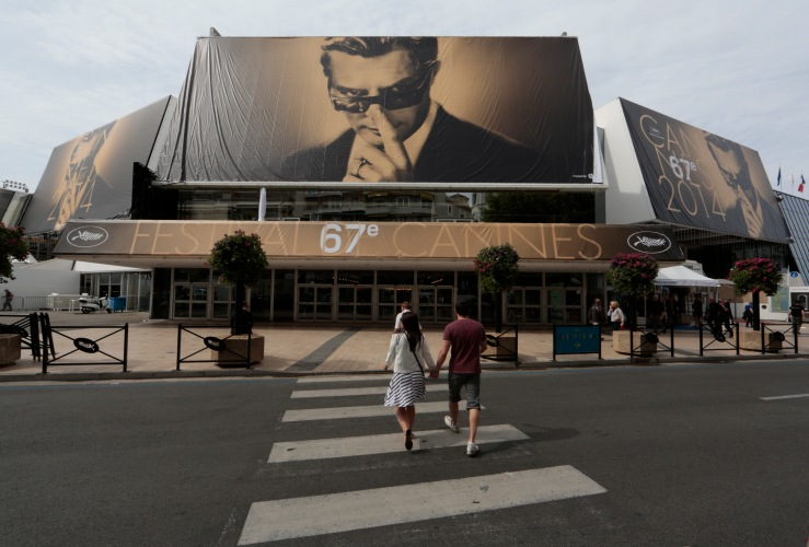 People walk past the Festival Palace displaying a giant canvas of the official poster of the 67th Cannes Film Festival featuring actor Marcello Mastroianni in Cannes