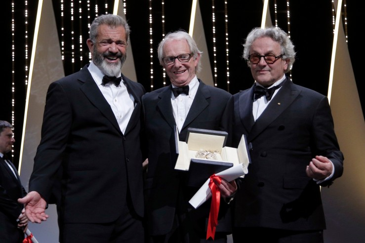 Director Ken Loach, centre, actor Mel Gibson, left and President of the Jury George Miller react after Roach is awarded the Palme d'or for the film I, Daniel Blake, during the awards ceremony at the 69th international film festival, Cannes, southern France, Sunday, May 22, 2016. (AP Photo/Thibault Camus)