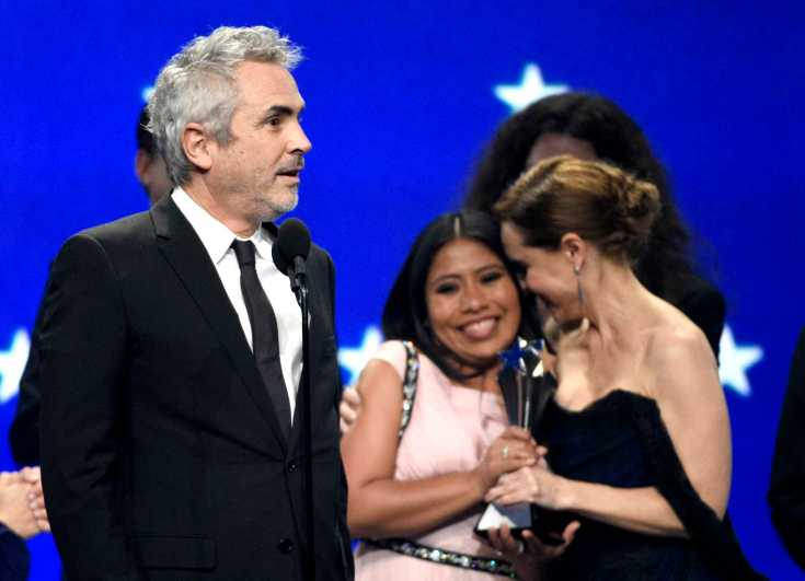 "Alfonso Cuaron, from left, accepts the award for best picture for ""Roma"" as Yalitza Aparicio and Marina De Tavira react at the 24th annual Critics' Choice Awards on Sunday, Jan. 13, 2019, at the Barker Hangar in Santa Monica, Calif. (Photo by Chris Pizzello/Invision/AP)"